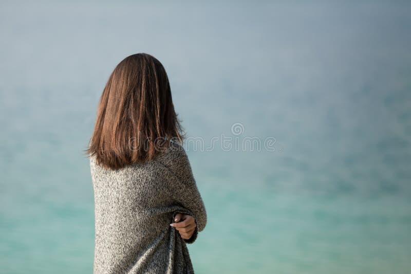 Härligt ung flickaanseende vid sjön royaltyfri foto