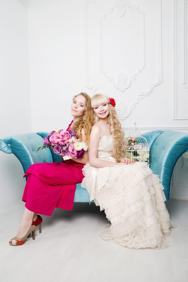 Härligt ung flickaståendesammanträde på den blåa soffan royaltyfri fotografi