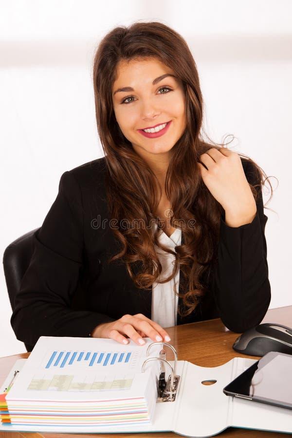 Härligt ungt arbete för brunettaffärskvinna i hennes kontor arkivbild