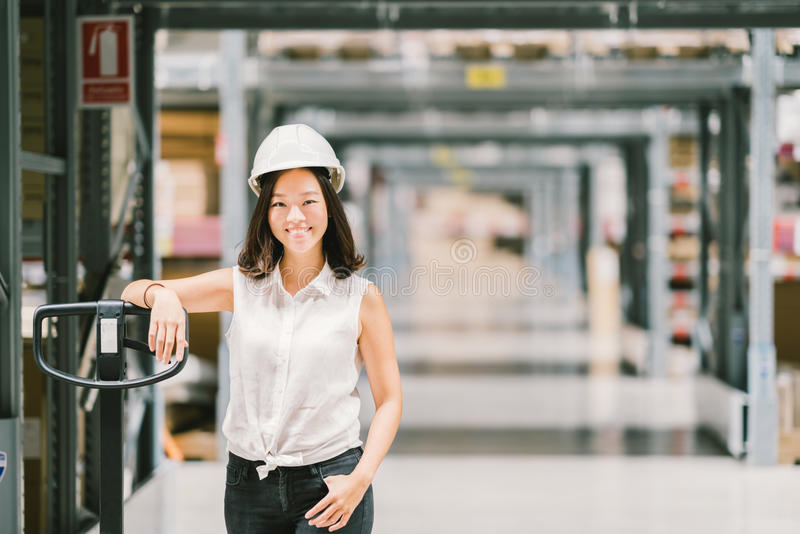 Härligt ungt asiatiskt le för tekniker- eller teknikerkvinna, lager- eller fabrikssuddighetsbakgrund, bransch eller logistiskt be royaltyfri foto