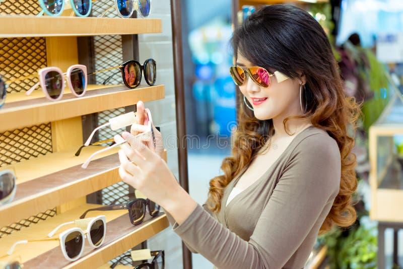 Härligt ungt asiatiskt shoppa för kvinna och vald solglasögon royaltyfria foton