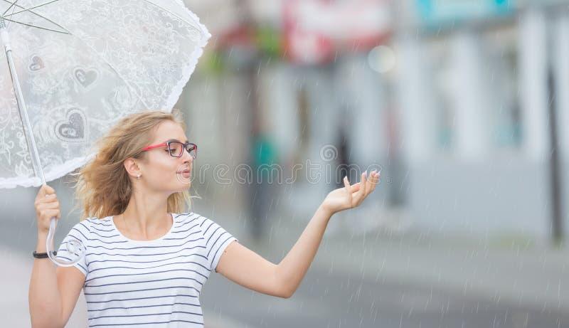 Härligt ungt blont flickainnehavparaply i sommarregn fotografering för bildbyråer