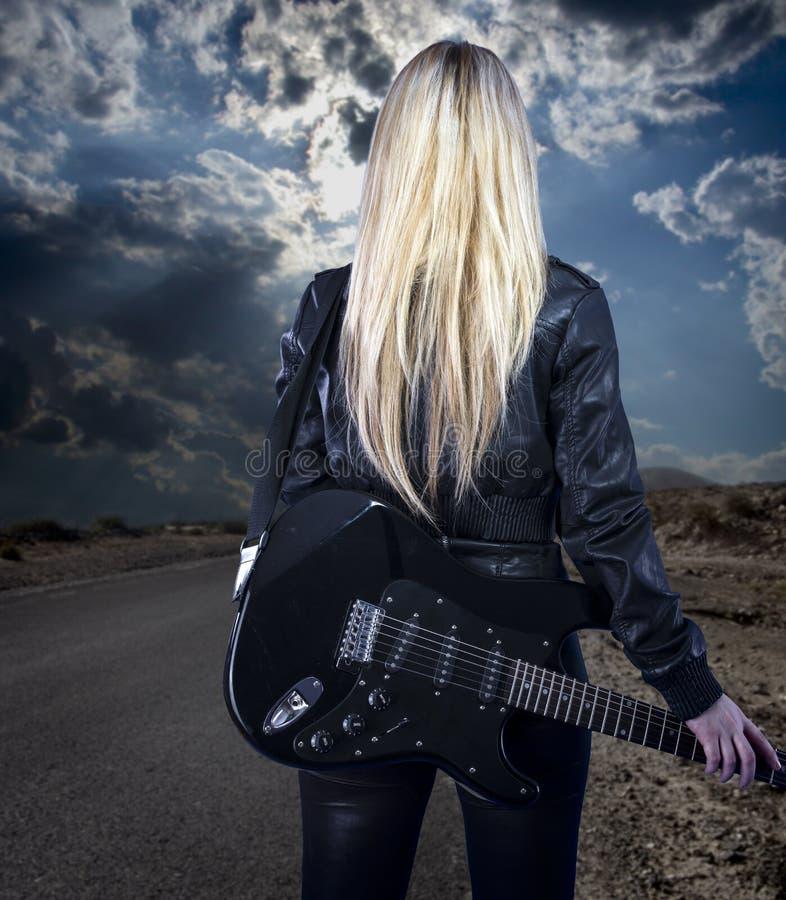 Härligt ungt blont iklätt svart läder med elektriska gu royaltyfri fotografi