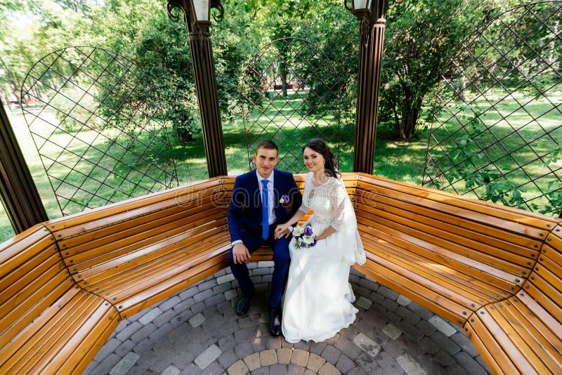 Härligt ungt brud- och brudgumsammanträde på en bänk och innehavhänder Gifta sig par som är förälskade på wedddagen fotografering för bildbyråer