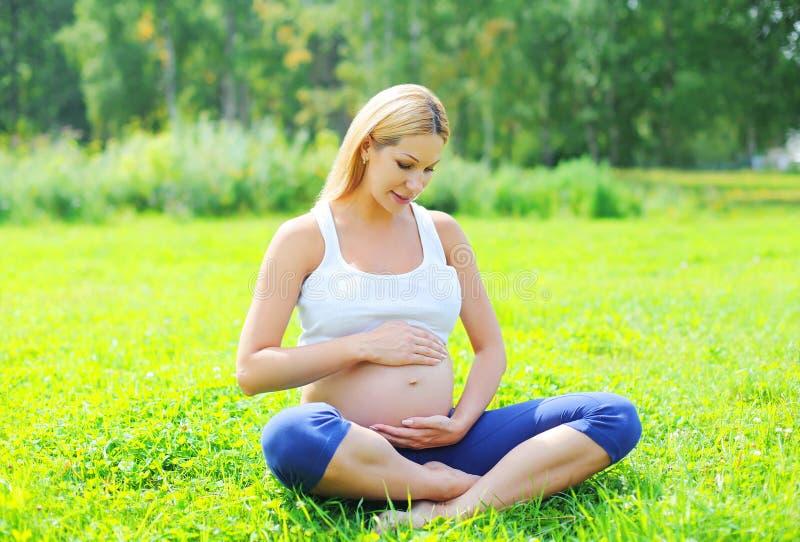 Härligt ungt gravid kvinnasammanträde på gräs som gör yoga i solig sommar royaltyfri bild