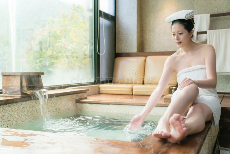 Härligt ungt japanskt damsammanträde på poolside fotografering för bildbyråer