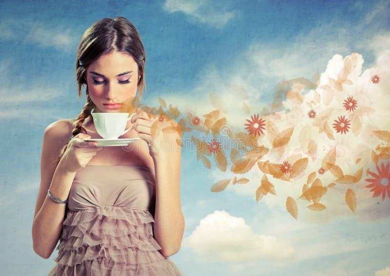 Härligt ungt kvinnainnehav en kupa av tea över en skybakgrund royaltyfri bild
