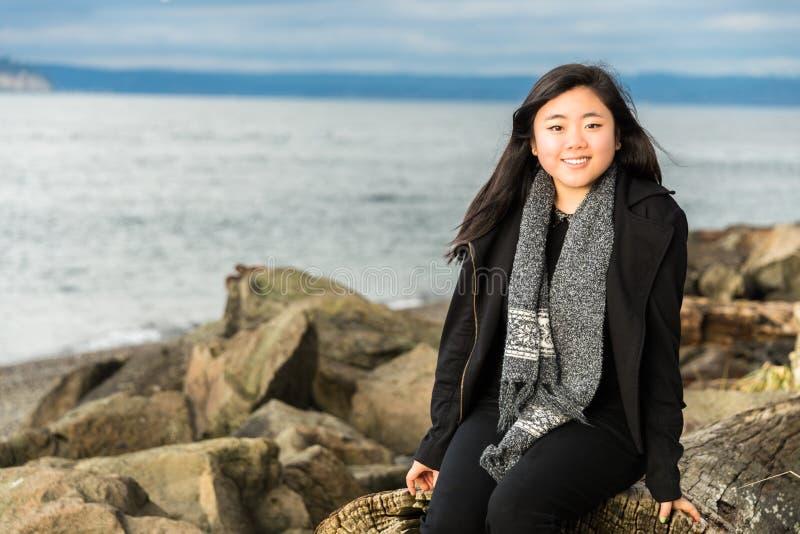 Härligt ungt kvinnasammanträde på strandDriftwood fotografering för bildbyråer