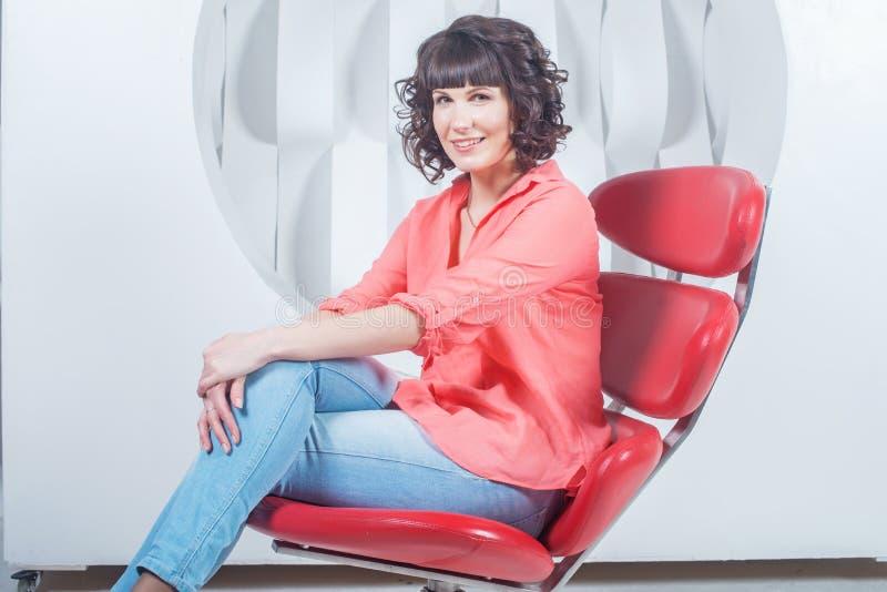 Härligt ungt säkert kvinnasammanträde i röd stol mot den vita väggen royaltyfri bild