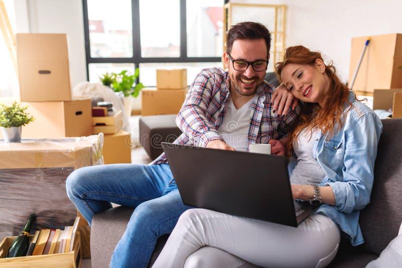 Härligt ungt shoppa för par som är on-line genom att använda en bärbar datordator och le, medan sitta i deras nya lägenhet efter  royaltyfria bilder