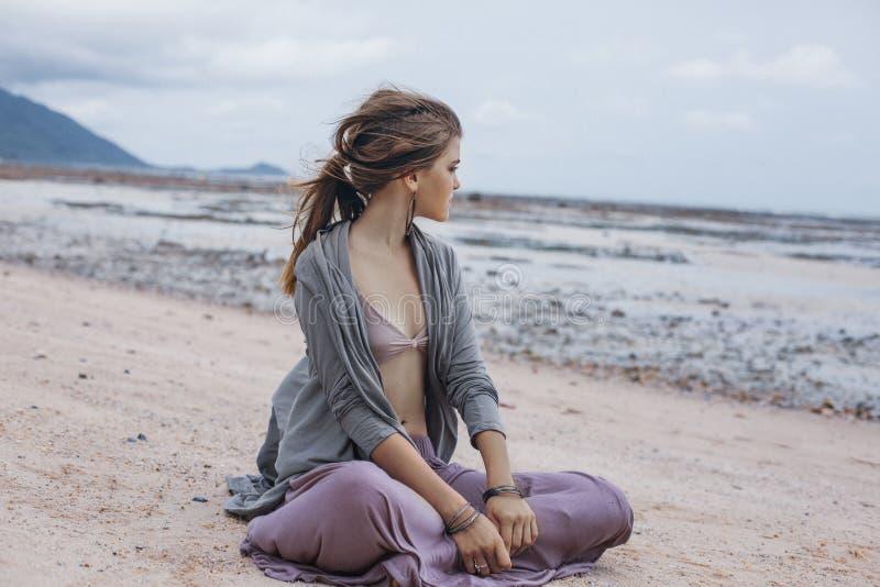 Härligt ungt stilfullt kvinnasammanträde på sand på stranden arkivbilder