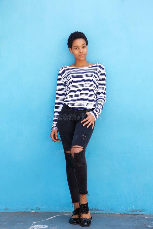 Härligt ungt svart kvinnaanseende för full längd mot den blåa väggen royaltyfri foto
