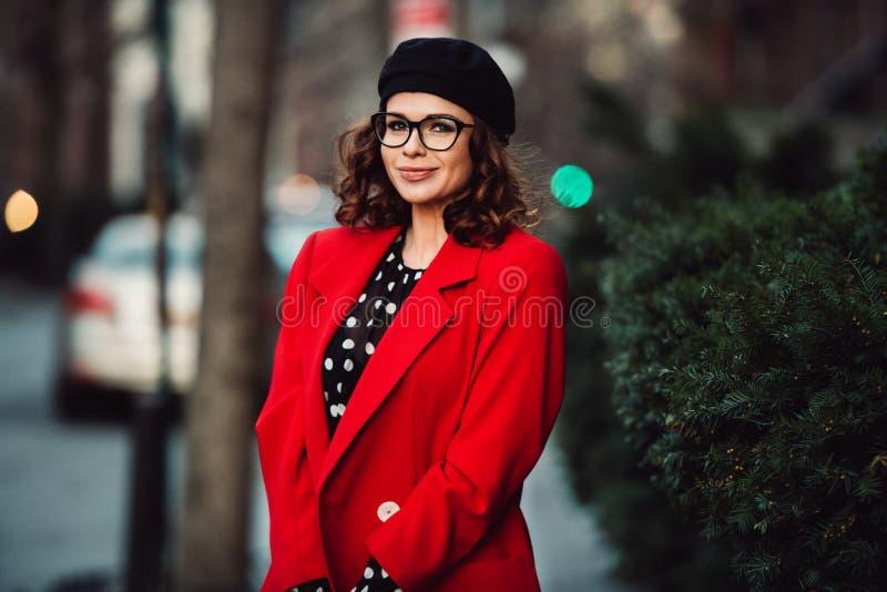 Härligt ungt vuxet bärande glasögon för yrkesmässig kvinna och stående det fria för röd dräkt på stadsgatan royaltyfri bild