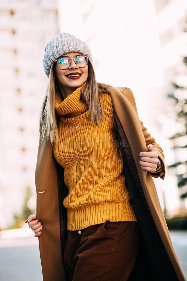 härligt utomhus- ståendekvinnabarn Modellera den bärande senapsgula tröjan, det beigea laget och den stilfulla stack hatten flick arkivbilder