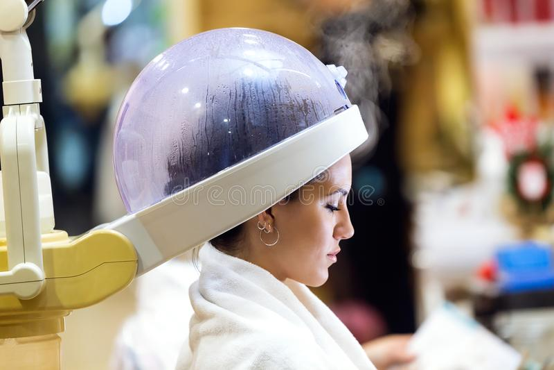 Härligt uttorkninghår för ung kvinna under maskinen i en skönhetsalong arkivfoton