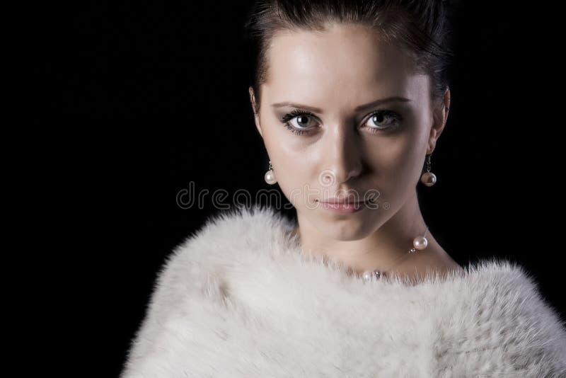 Ståenden av skönhetkvinnan i lyxig vit pälsfodrar täcker royaltyfria bilder