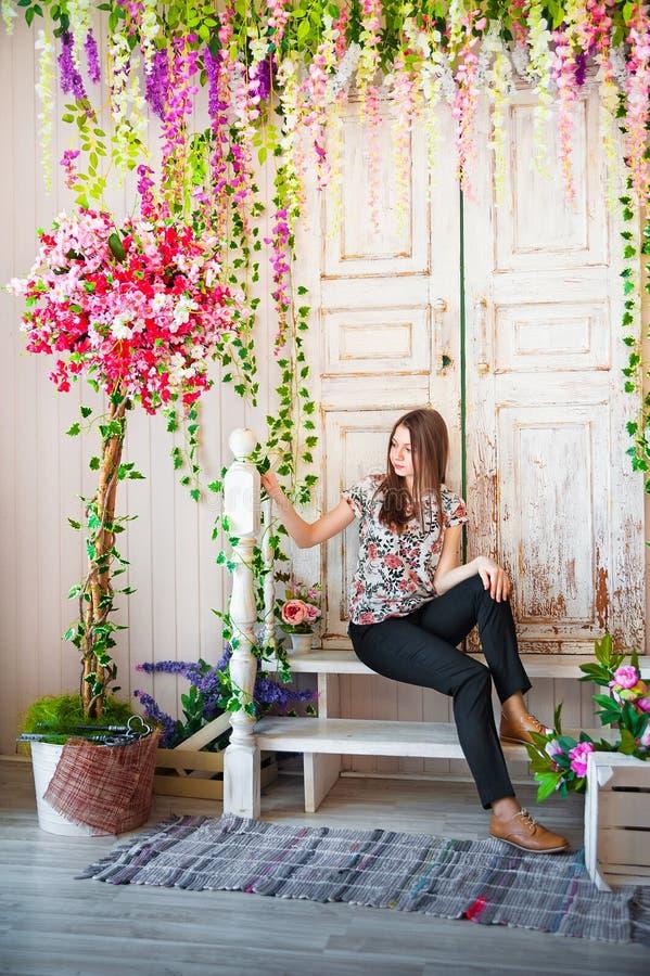 Härligt vårfotografi i den dekorerade inre En ung kvinna i blommor royaltyfria foton