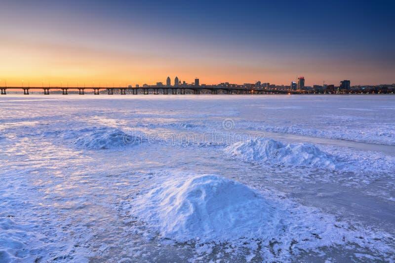 Härligt vinterlandskap med den djupfrysta floden på skymning I royaltyfri bild