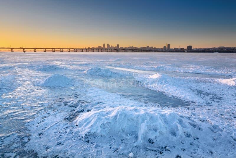 Härligt vinterlandskap med djupfryst flod- och solnedgånghimmel I arkivfoton