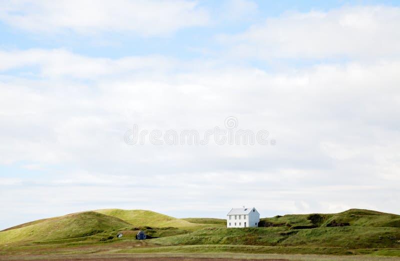 Härligt vitt hus mot molnig himmel i Island royaltyfri bild