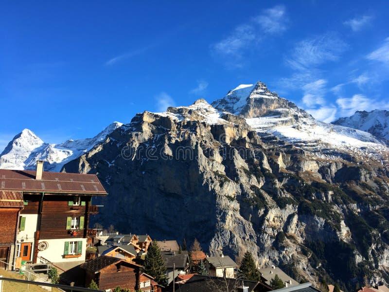 Härligt vitt moln med blå himmel överst av stenberget och vit snö som täckas i eftermiddagen royaltyfria bilder