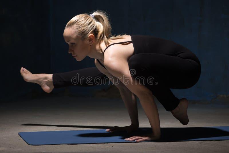 Härligt yogakvinnaanseende i Eka Pada Bakasana 2 arkivbilder