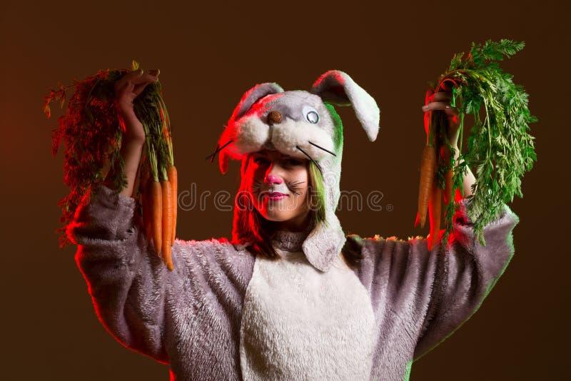 Häschenmädchen mit Karotten stockbilder