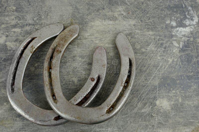 Häst- dem med gamla slitna hästskor på en skrapad och skadad stålbakgrund Massor av textur med kopieringsutrymme fotografering för bildbyråer
