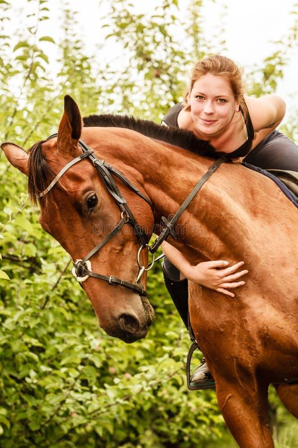 Häst för ridning för kvinnajockeyutbildning En cyklist- eller cyklistridning längs en konkret cykelbana royaltyfria bilder