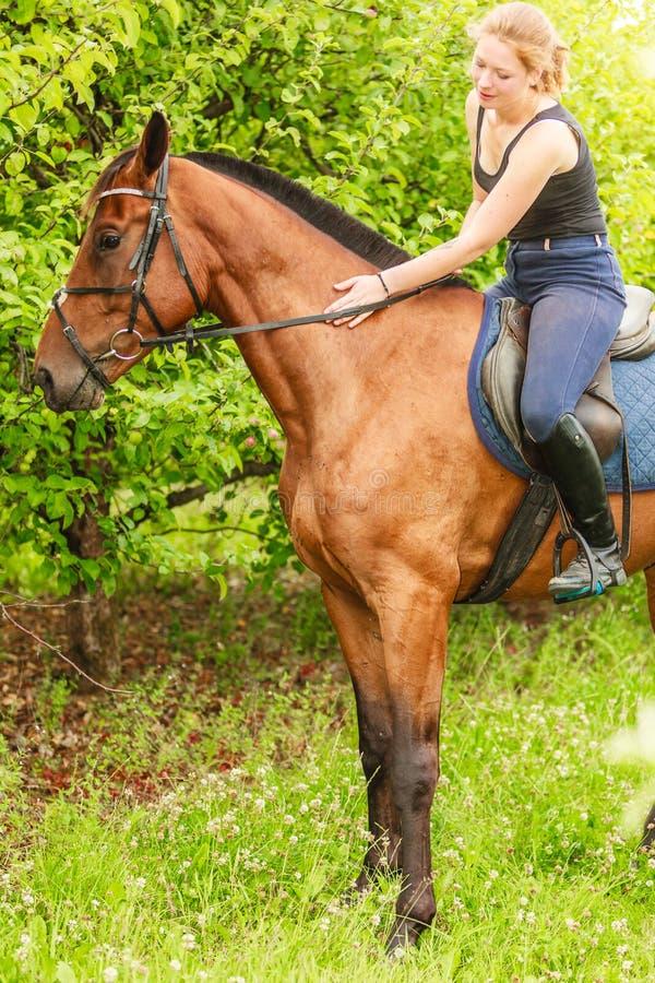 Häst för ridning för kvinnajockeyutbildning En cyklist- eller cyklistridning längs en konkret cykelbana royaltyfri bild