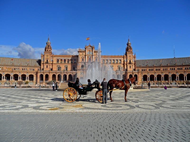 Hästdragen vagn som är främst av den Vicente Traver springbrunnen på den Plaza de Espana fyrkanten i Seville, Spanien arkivbilder