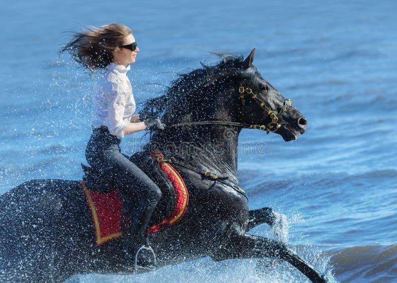 Hästkvinnan och spanjorhästen rusar spring in i havet fotografering för bildbyråer