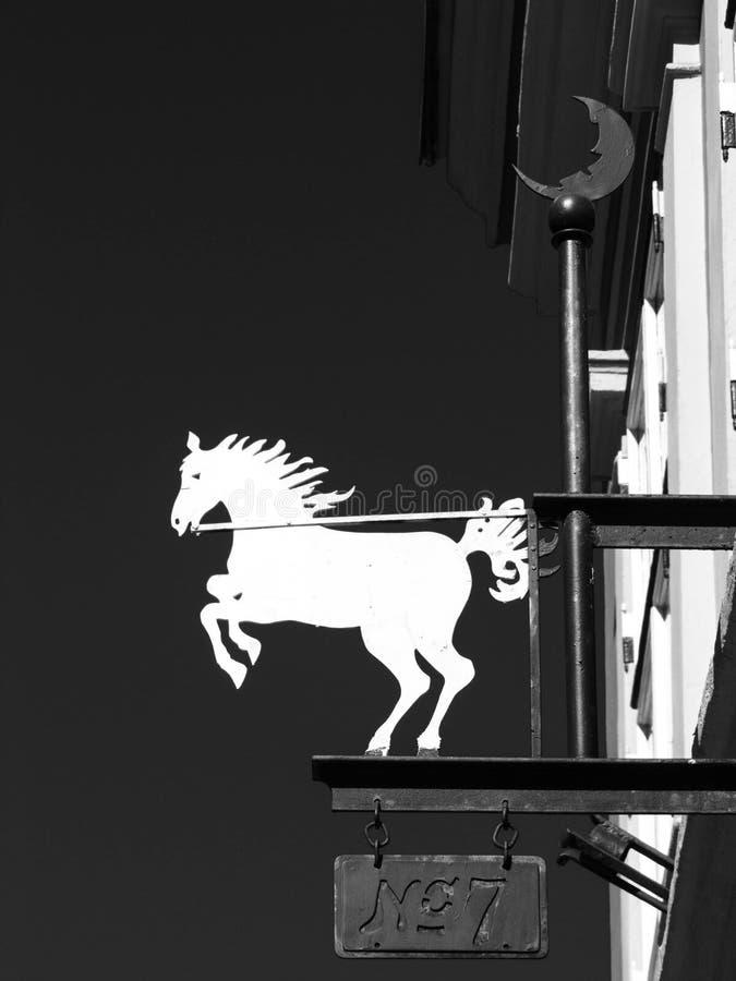 Hästtecken för vit metall framme av ett hus royaltyfria bilder