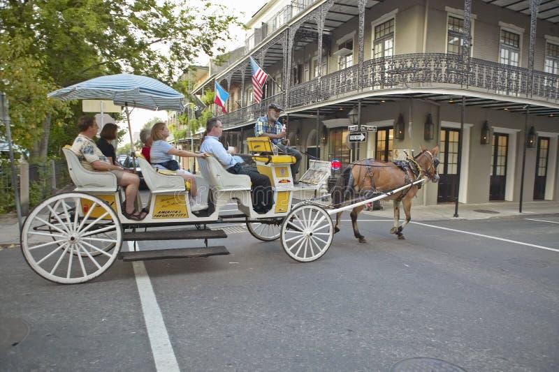 Hästvagn och turister i fransk fjärdedel av New Orleans, Louisiana royaltyfri foto