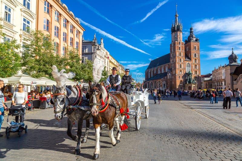 Hästvagnar på den huvudsakliga fyrkanten i Krakow arkivfoto