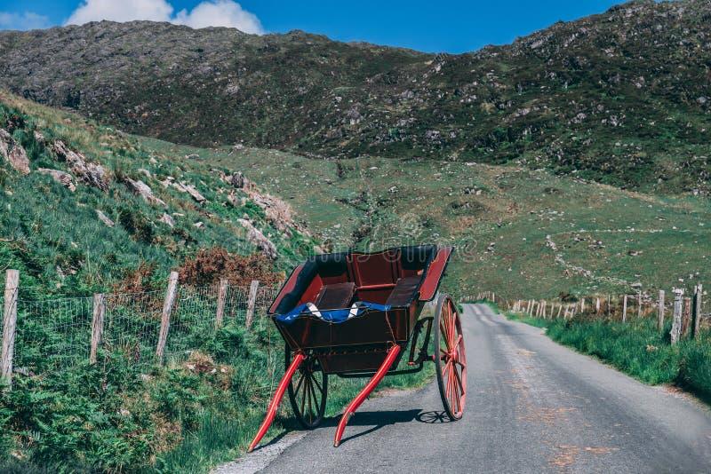 Hästvagnen ligger på den sceniska vägen av Gap av Dunloe, ett smalt bergpasserande i ståndsmässiga Kerry, Irland på en solig dag royaltyfri bild
