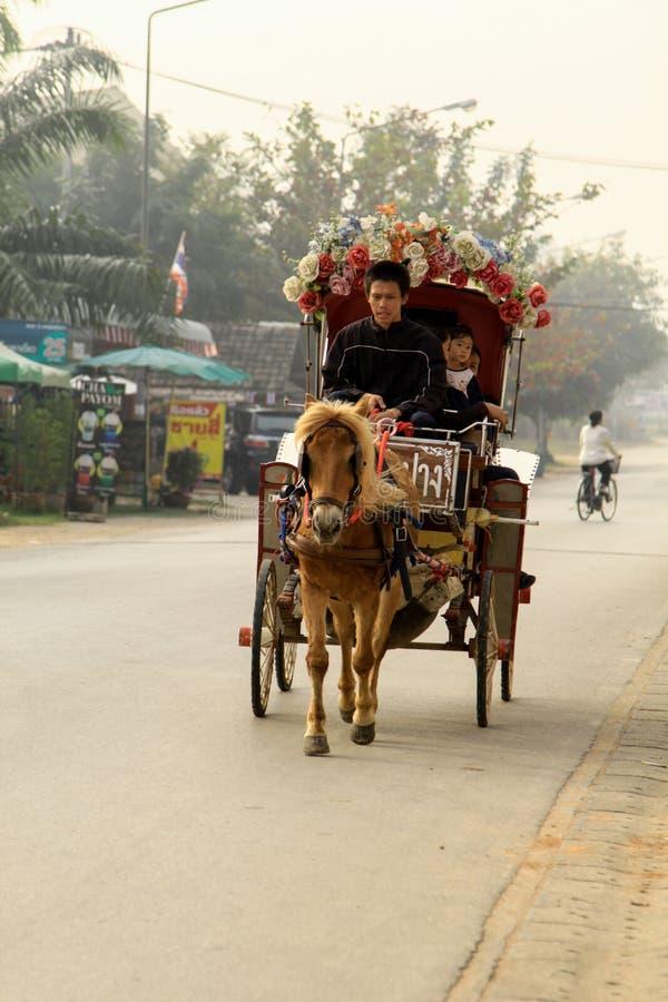 Hästvagnen med folk i Lampang på Wat Phra That Lampa fotografering för bildbyråer