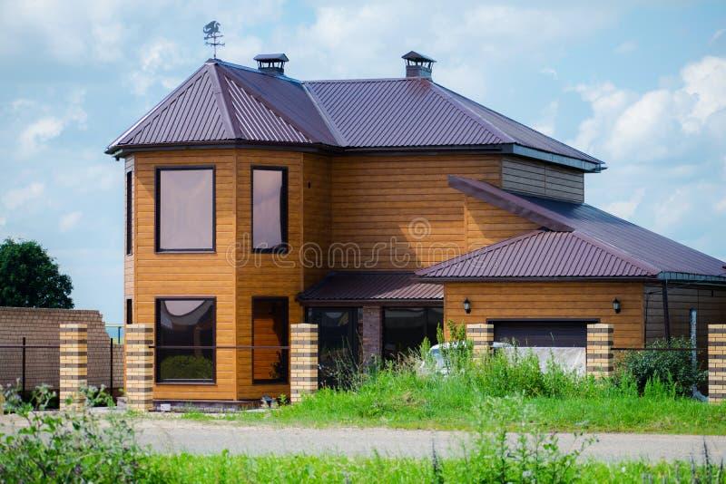 Häuschen mit zwei Geschossen mit Garage in einem Dorf mit schöner Natur Die Fassade des Hauses lizenzfreie stockbilder