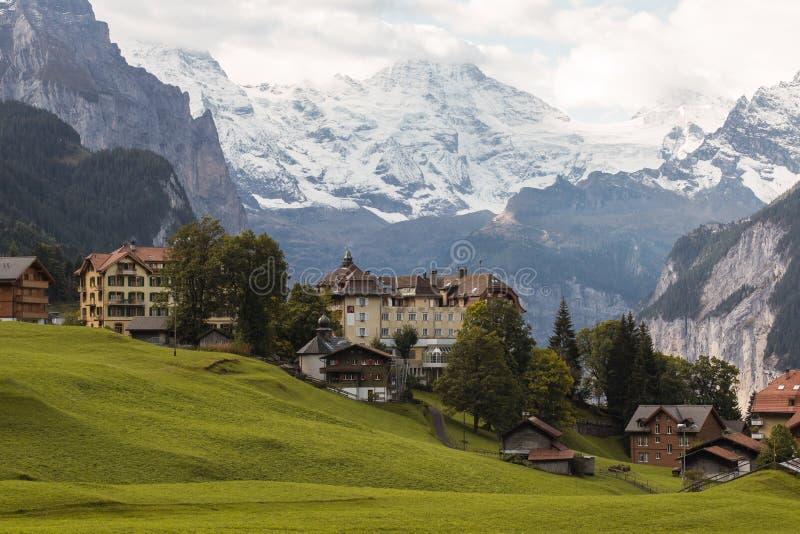 Häuser auf einem grünen Hügel mit Gebirgshintergrund stockfotografie