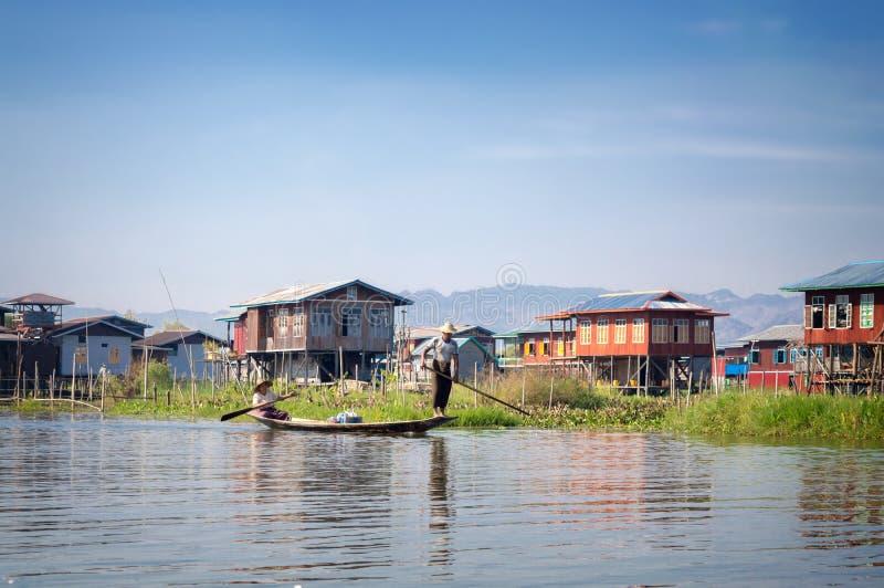 Häuser auf hölzernen Stapel und birmanische Leute in einem Boot in einem Dorf am Inle See, Birma Myanmar lizenzfreie stockfotos