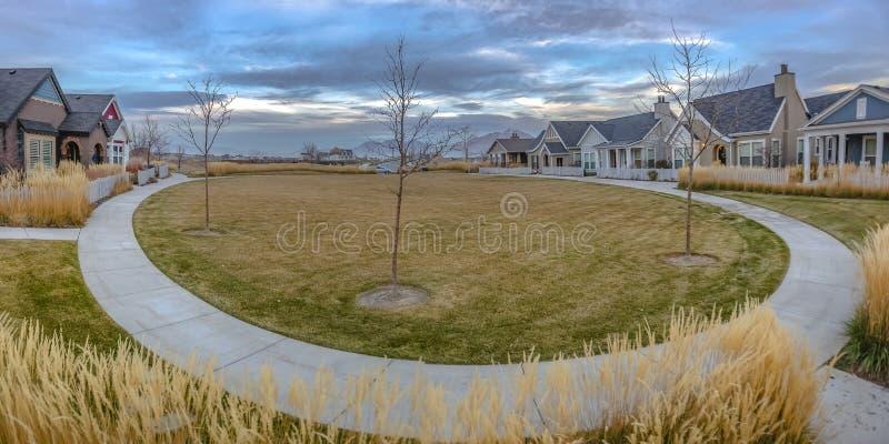 Häuser entlang einem Kreisweg gegen bewölkten Himmel lizenzfreie stockfotografie