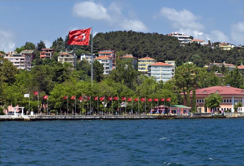 Häuser entlang und türkische Markierungsfahne der Bosporus die Türkei lizenzfreies stockfoto