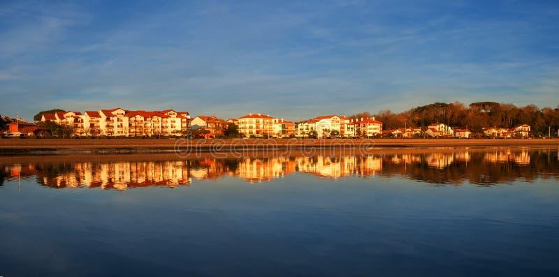 Häuser reflektierten sich im Wasser des Strandes bei Sonnenuntergang, Hendaia stockfotografie