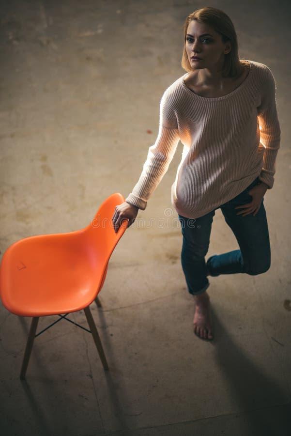 Häuslicher Komfort mit Mädchen am Stuhl durchdachte Frau zu Hause mit orange Stuhl Fauler Tag zu Hause Frustrierte Frauenstellung stockfotos