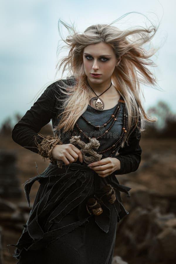 Häxa i en lång svart klänning arkivfoto
