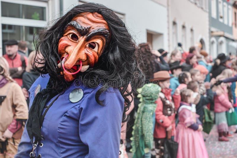 Häxan med en lång näsa ser awkwardy på kameran Gatakarneval i den sydliga Tyskland - svart skog arkivbilder