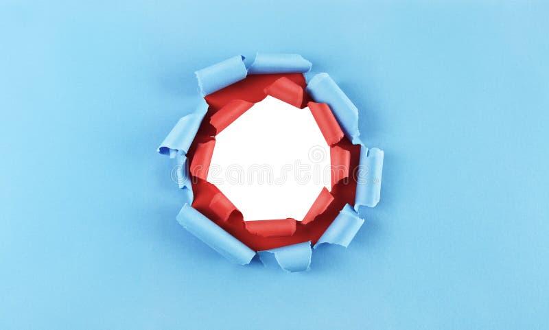 Hål i blått och rött papper royaltyfria foton