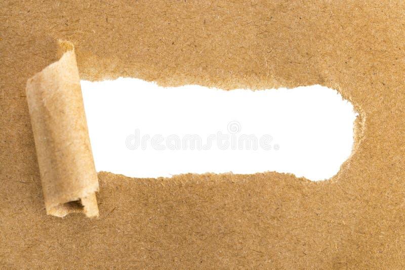 Hål i brunt papper med sönderrivna sidor över pappers- bakgrund med arkivfoton