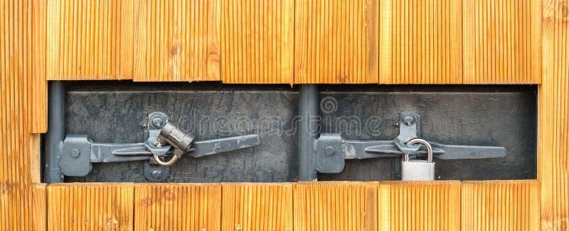 Hål i en trävägg med två hänglås på en grå metallisk dörr arkivfoton