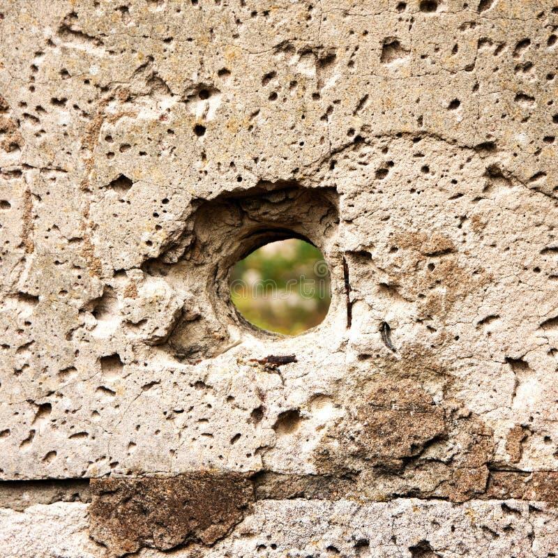 Hål i förstörelsebetongväggen, kulhål, fritt utrymme för abstrakt bakgrund för design efter krig arkivfoto